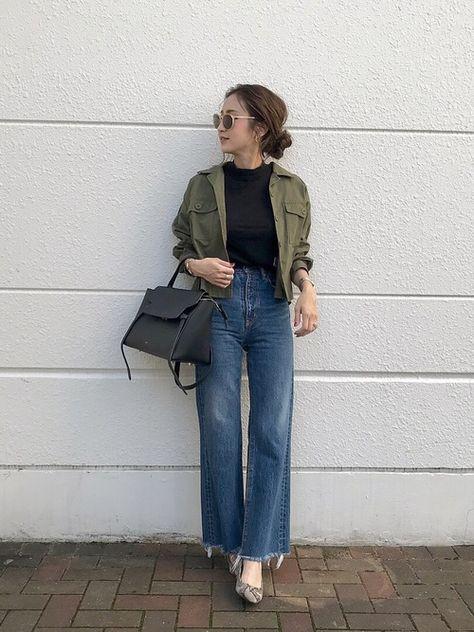 parka verde militar, blusa preta e calça jeans