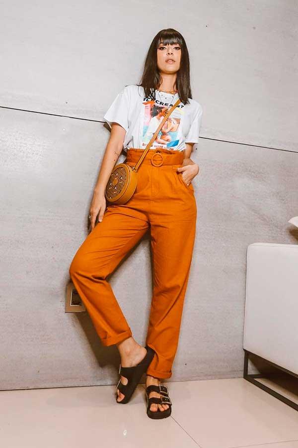 calça social laranja, t-shirt e birken