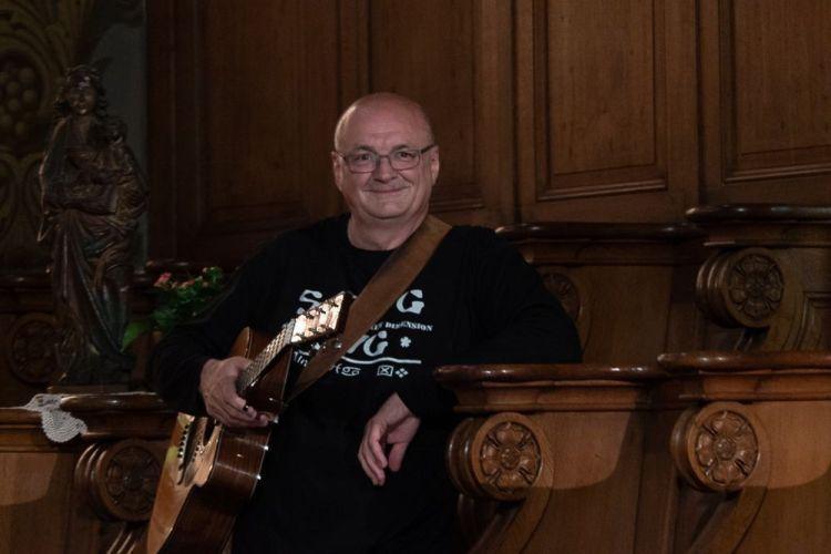 Dans le viseur de mon appareil photo, zoom déployé au maximum, j'aperçois Jacques Stotzem, guitare en main qui piaffe à la sortie de la sacristie. Il a l'air impatient et un petit sourire gourmand.