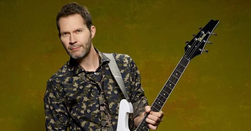 Paul Gilbert segurando uma guitarra branca