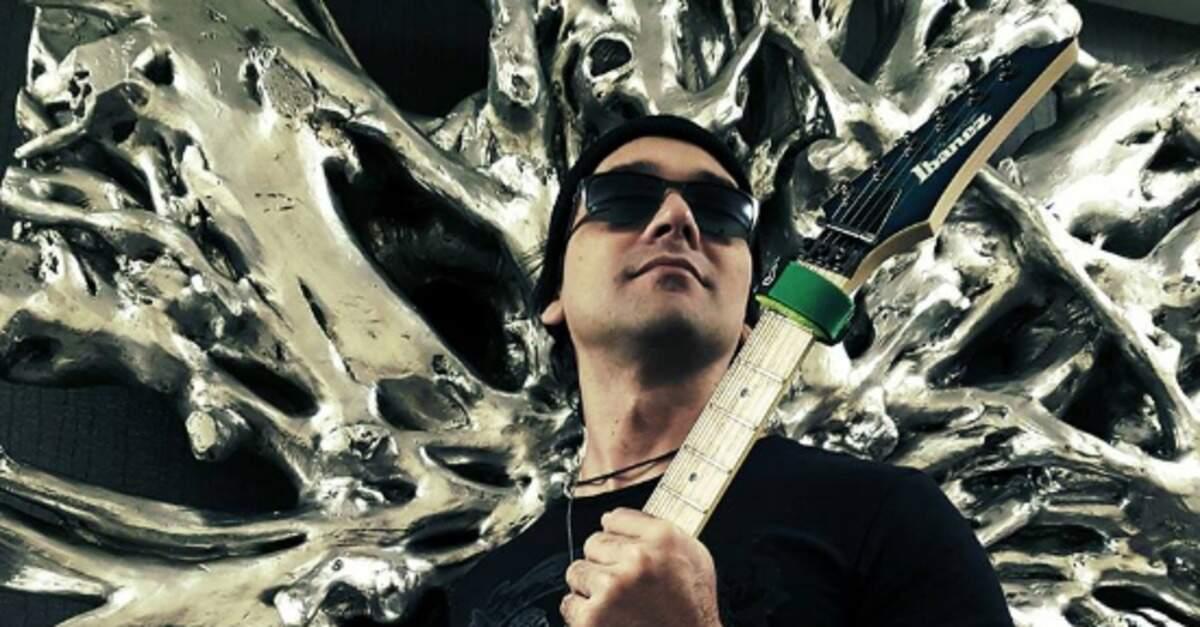 Dallton Santos segurando uma guitarra Ibanez