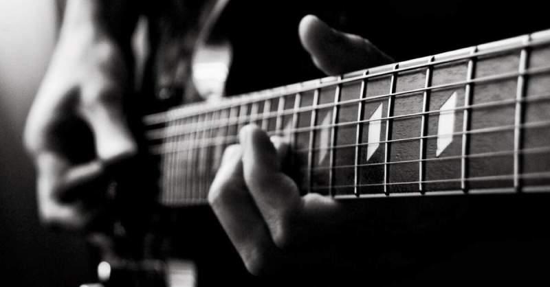 Foto em preto e branco de um músico tocando guitarra