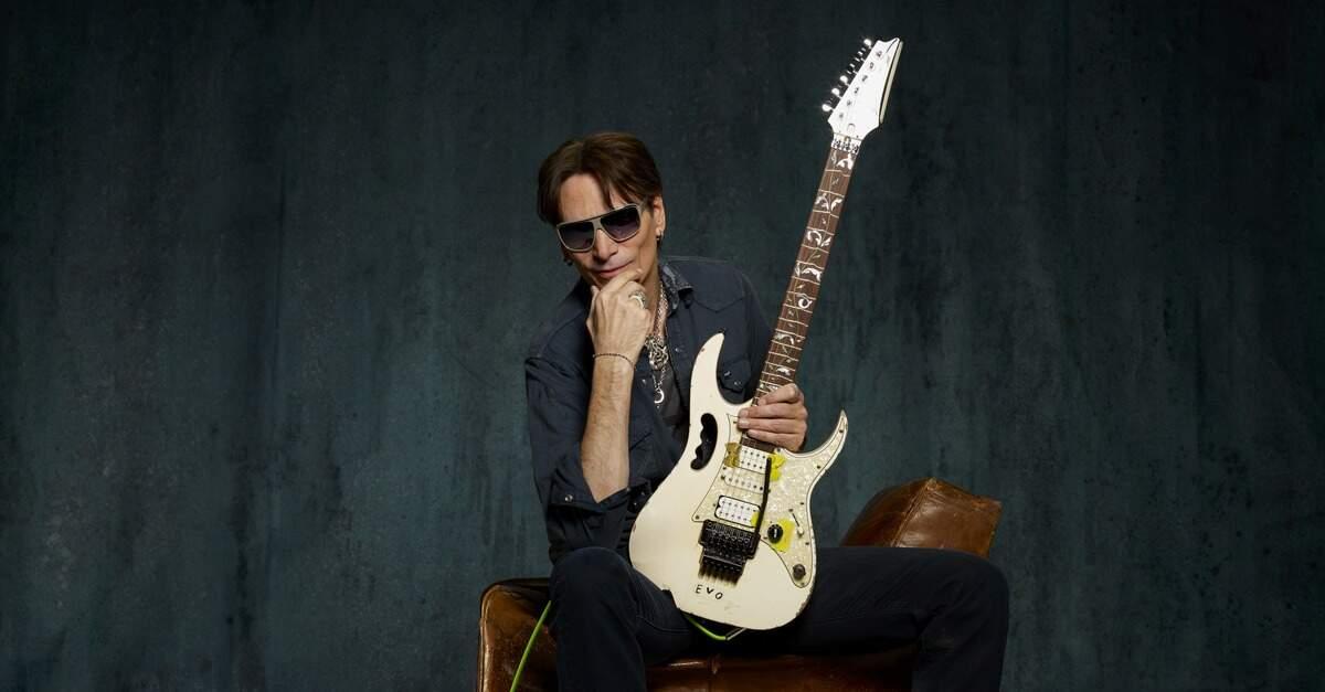 Steve Vai sentado em um sofá com uma guitarra Ibanez