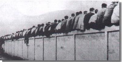Fan Barcelona menyaksikan pertandingan dengan duduk pada bagian tembok tribun.