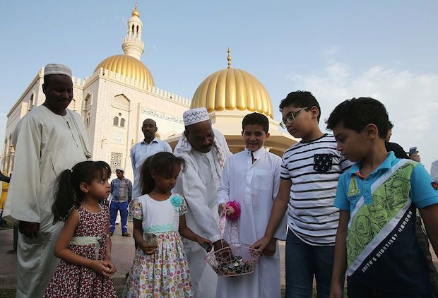Muslim children distribute chocolates at the end of the morning Eid al-Adha prayer outside a mosque in the Omani capital Muscat.