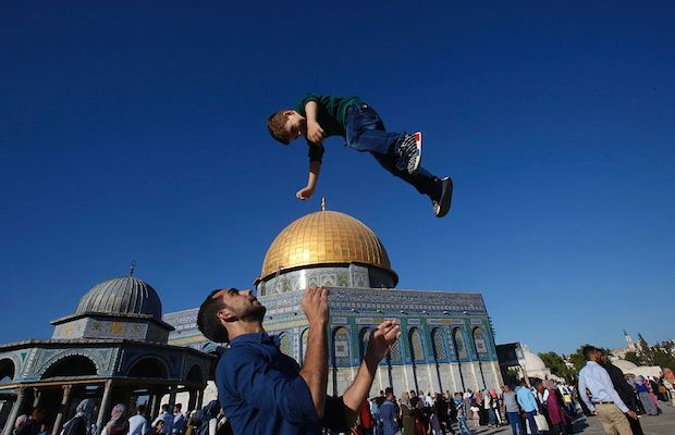 A Palestinian man plays with a kid outside the Dome of the Rock in Jerusalem's Al-Aqsa mosque compound following Eid prayers.