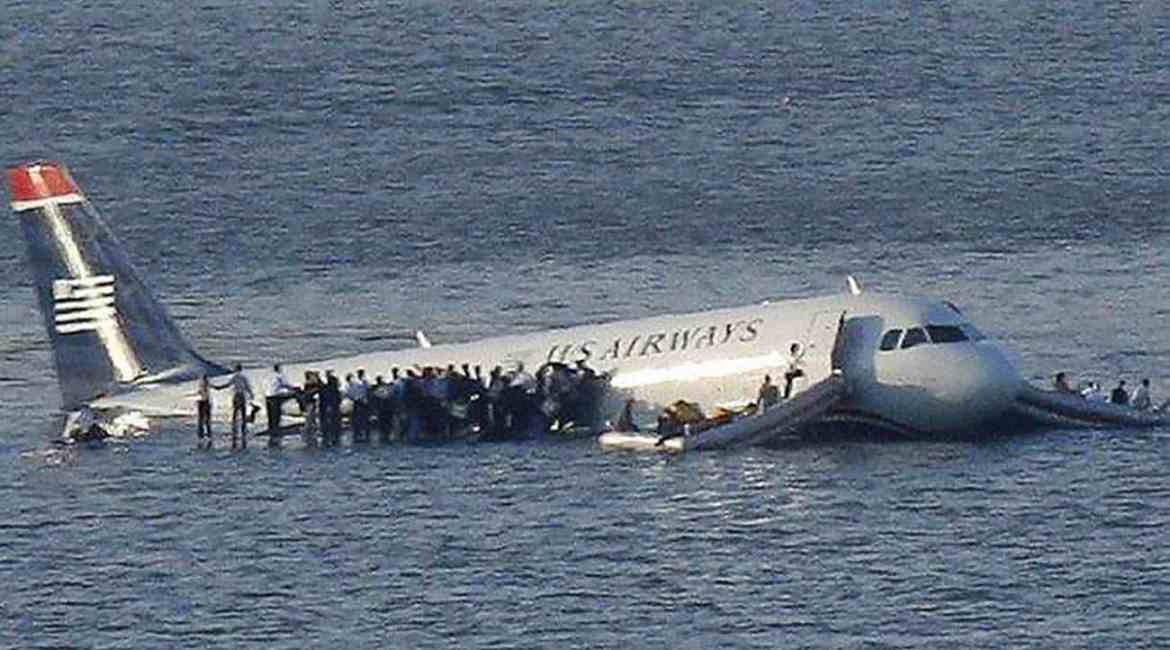 US Airways Flight # 1549 in the Hudson River with passenger on the wing awaiting rescue.