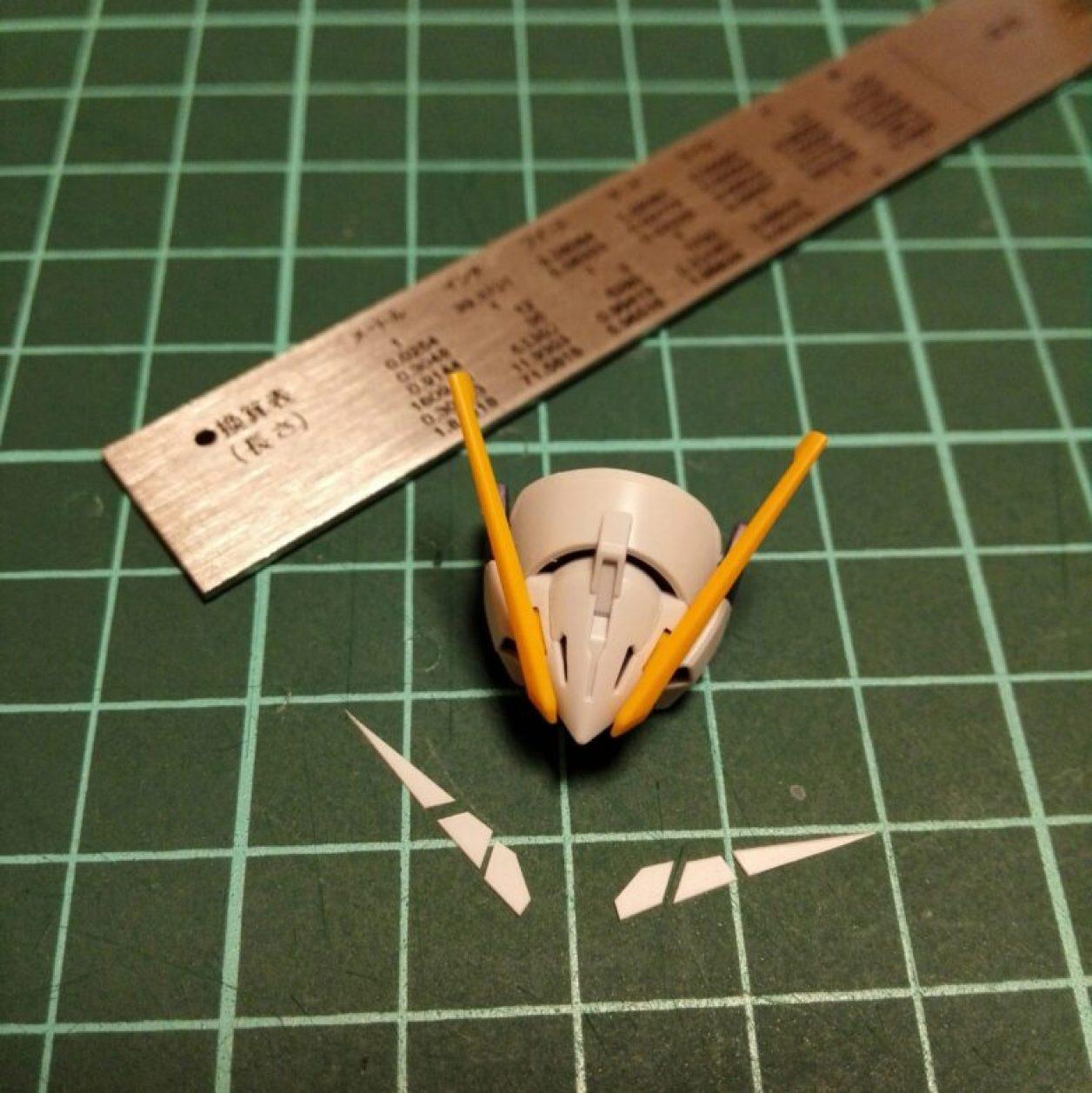 プレミアムバンダイ限定販売のhguc ガンダムtr-6[ウーンドウォート]の自作アンテナを造るためにプラバンを切り出してズレないようにマスキングテープで固定してアンテナ状に切り出し、切れ込みを入れた画像