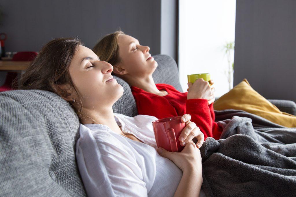 Mulheres Vivendo uma Experiência de Inverno com canecas de café na mão.