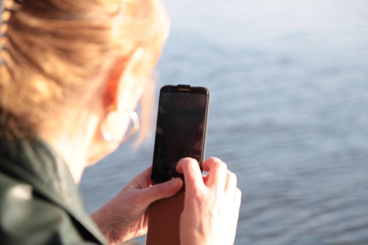 Gunilla Larsdotter vid vattnet, med mobilen som arbetsredskap