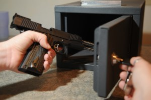 Woman putting her unloaded handgun into a safe