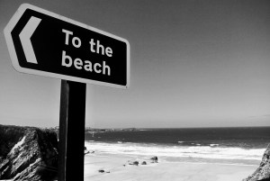 Black and white photo of a sign pointing to the beach