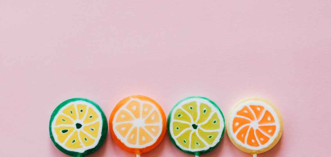 assorted colorful lollipops on pink background