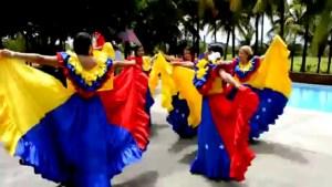 Mujeres con traje típico de la bandera venezolana bailando joropo