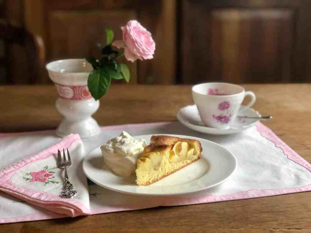 Gedeckter Tisch mit Kaffee und Apfelkuchen.