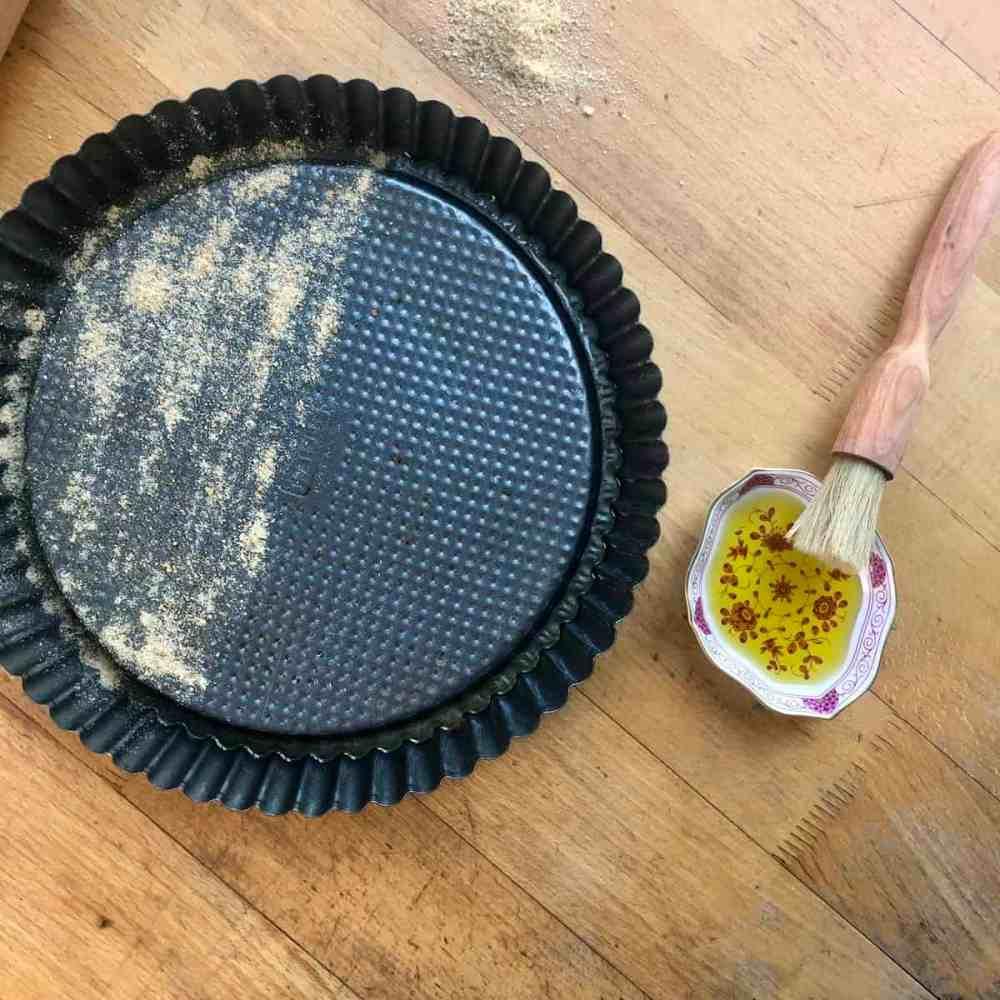 Quicheform mit Öl und Semmelbrösel vorbereiten.