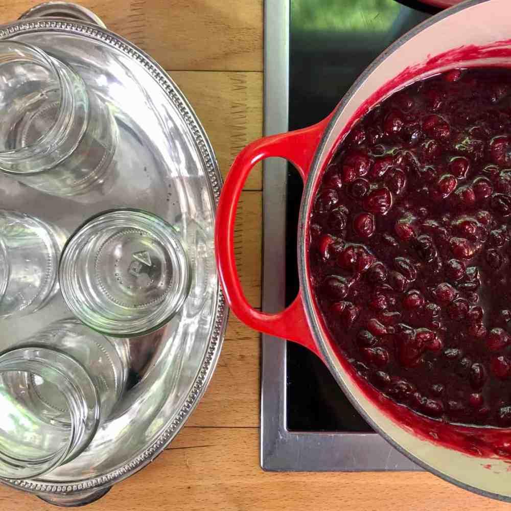 Fülle die heiße Marmelade vorsichtig in die vorbereiteten Gläser.