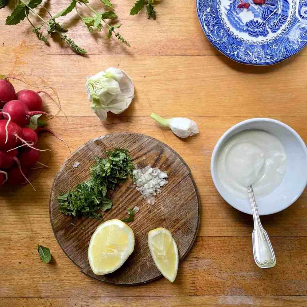 In einer Salatschüssel den Joghurt, Knoblauch und den Saft der halben Zitrone vermischen.