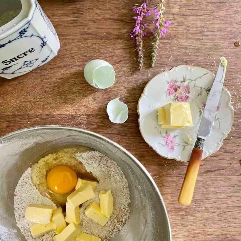 Das Ei, Salz und die kalte Butter in Stücken dazu geben.