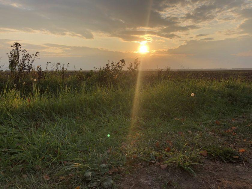 Sonnenuntergan auf einem Feld in der Nähe der Berges der Kreuze in Litauen