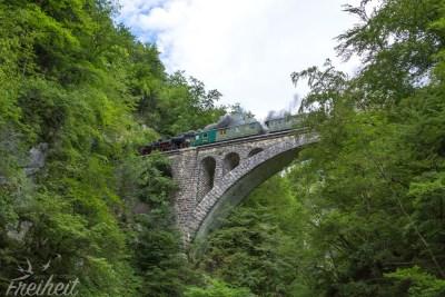 Über dem Damm rauscht eine Dampfeisenbahn hinweg