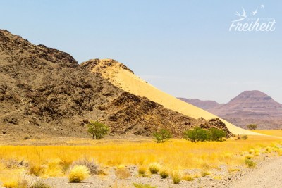 Ein Hügel aus Fels auf der einen Seite und Sand auf der anderen