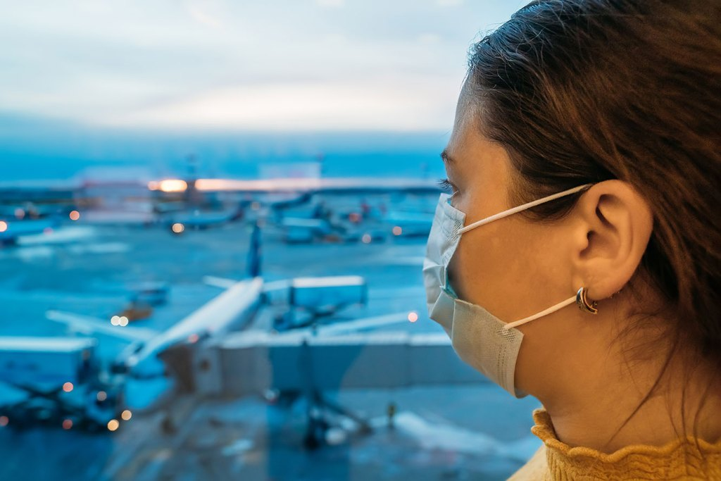 woman wearing mask in airport terminal
