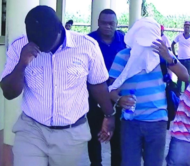 The two officers covered their faces as they are being led away by Detective Sergeant Lawrence Thomas