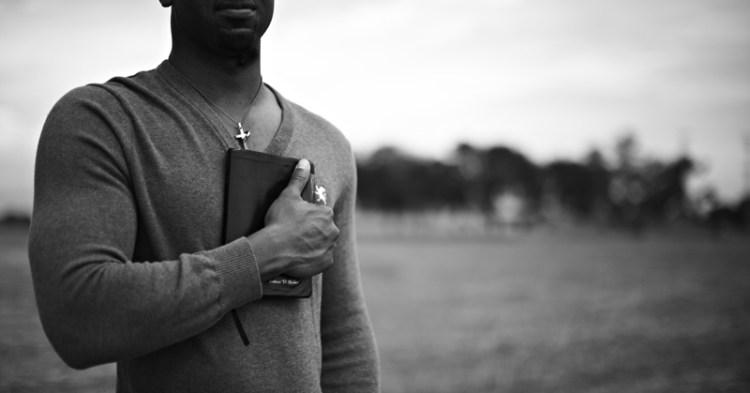 chretien noir avec une bible sur le poitrine