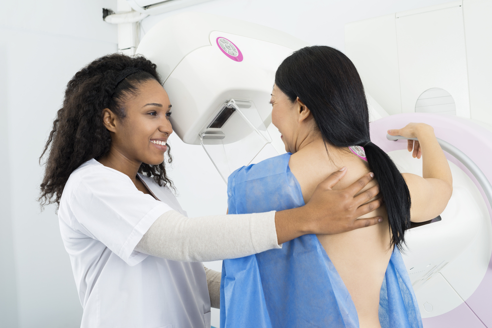 Doctor Assisting Woman Undergoing Mammogram