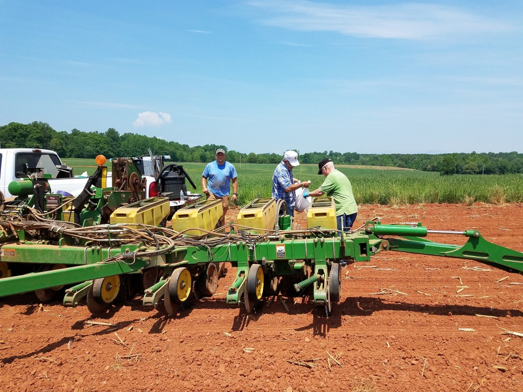 L to R, Johnathan Inskeep, John Helvey and Don Meek plant 24 corn varieties at Battle Park Farms in Culpeper County, May 14, 2018.  A field day is planned for September.