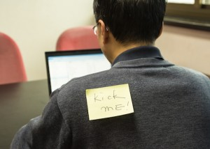 man with kick me sign on his back