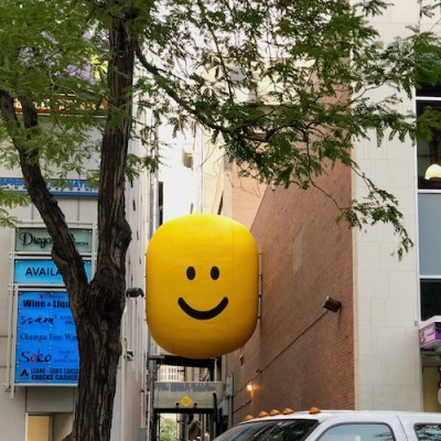 Smiley face icon stuck between two buildings above an alleyway