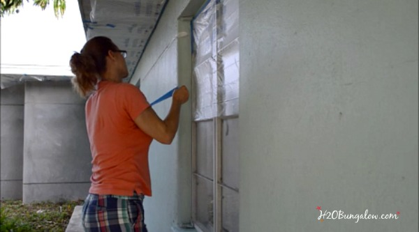 taping-window-prepping-to-paint-outside-of-home-with-paint-sprayer-2-H2OBungalow