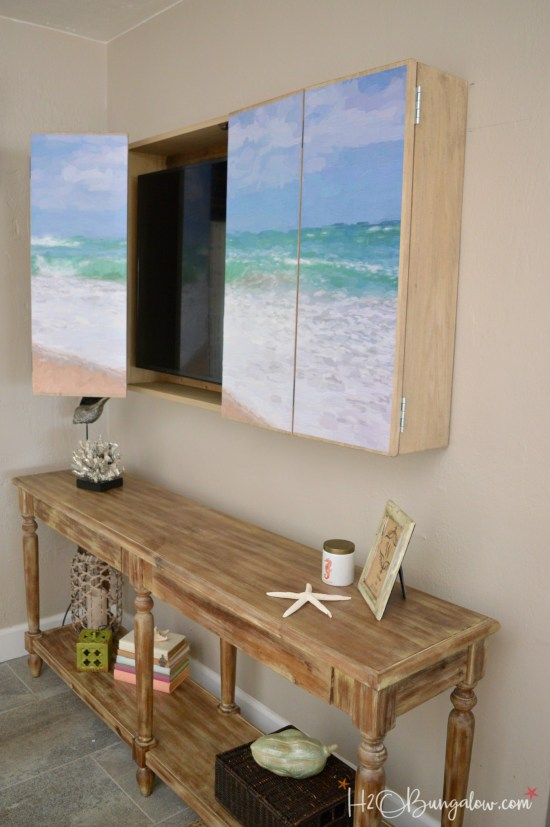 Free plans for a DIY wall mounted tv cabinet. Build a cabinet to hide the flat screen TV behind art in your home. Simple instructions for hidden tv cabinet you can make in a day.