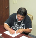 Ezequiel Nunez signs and assumes ownership of Habitat home