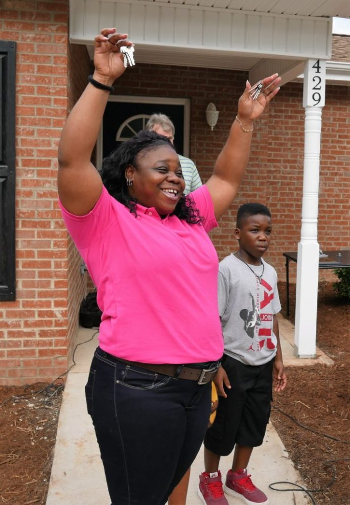 Ebone Moore and son Emmanuel expressing joy after receiving the keys to her home.