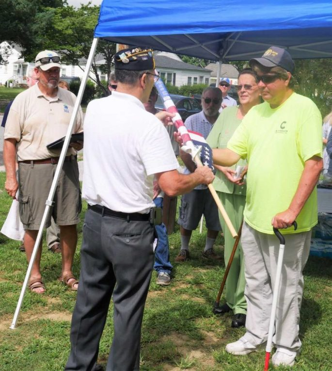 Rick Caparolle of American Legion post 126 presents a flag to Mike Lyens, a Navy veteran, at the dedication of the new home of Mike and his wife, Rebecca, at Mike's right. At far left is Bill Smith of Chowan-Perquimans Habitat for Humanity.