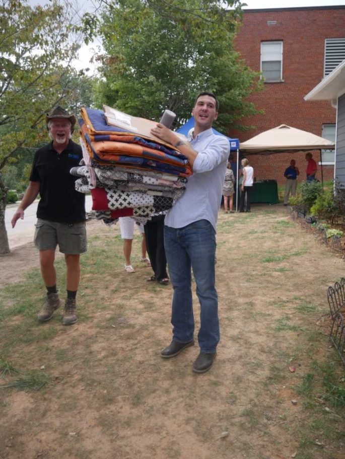 Steve Bruton, volunteer coordinator, and Casey Bailey, son of homeowner Cherrie Patrick. Casey holds a stack of quilts - one for each member of the family - made for them by a volunteer organization.