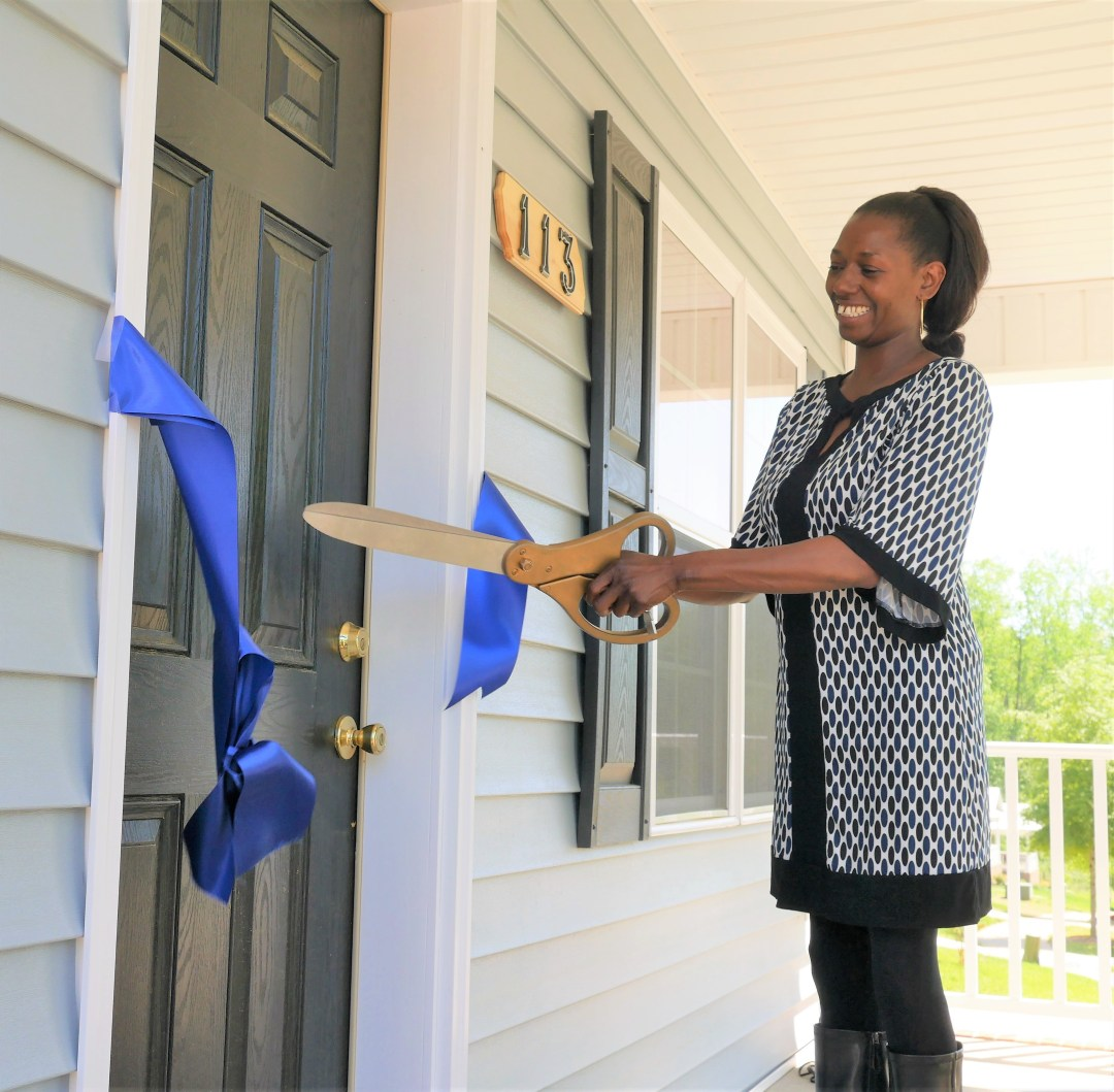 Perryrease Stinson cuts the ribbon before inviting guests at the dedication into her new Habitat for Humanity home.