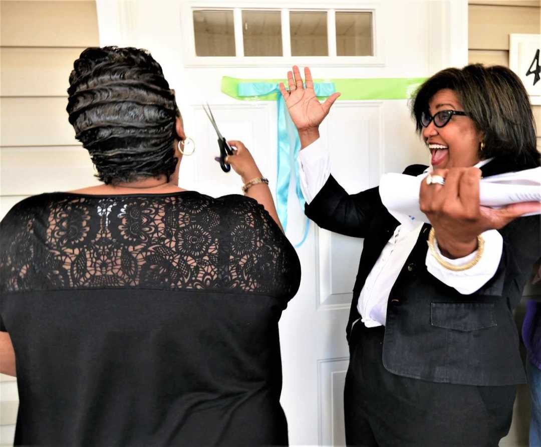 Fentress Gerald, right, of the State Employees Credit Union, leads the cheers as Khadijah Shabazz cuts the ribbon at her new home on Carver School Road in Winston-Salem.