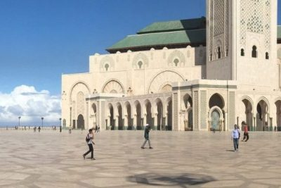 An exterior photograph of Hassan II Mosque in Casablanca. People are seen walking around the mosque's courtyard.