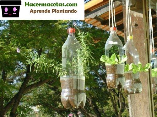 macetas hechas de botellas plasticas colgadas en el jardin