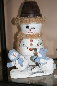 Bella macetas pintadas se transforman un coqueto hombre de las nieves con bufanda brillante y collar de luces de navidad