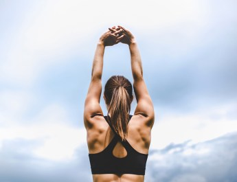 Sporty girl stretching arms above head