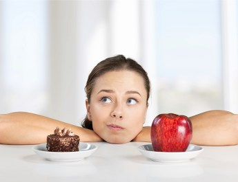 Woman looking at apple and chocolate cake
