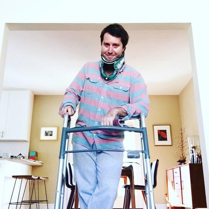 Graham posing in teal neck brace leaning against walker