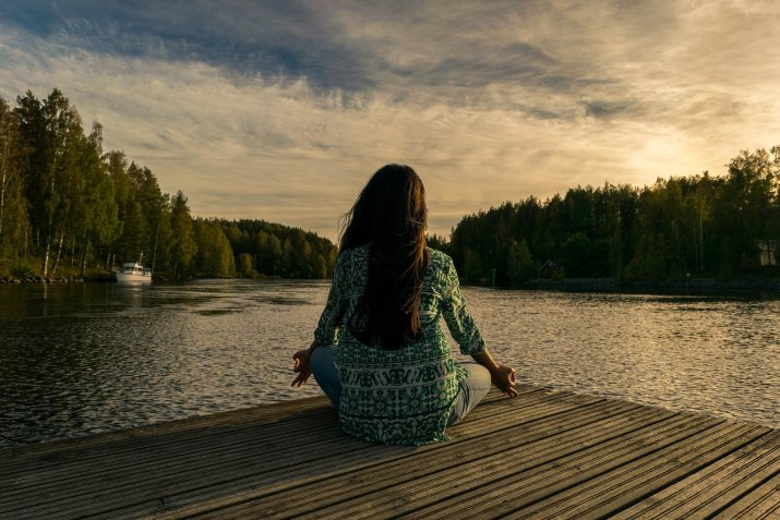 Photo of woman seen from behind sitting and meditating on the corner of a dock in front of a lake