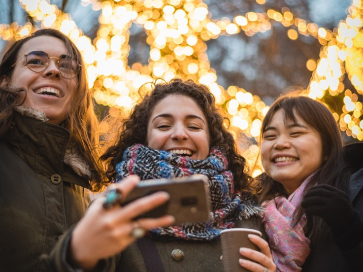 Three woman taking a selfie in front of sparkling lights
