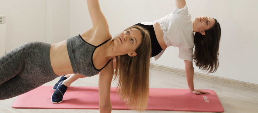 Two women performing side planks